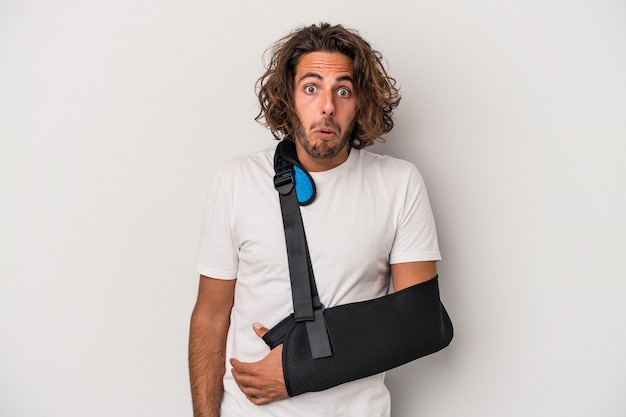 Young caucasian man with broken hand isolated on gray background shrugs shoulders and open eyes confused.