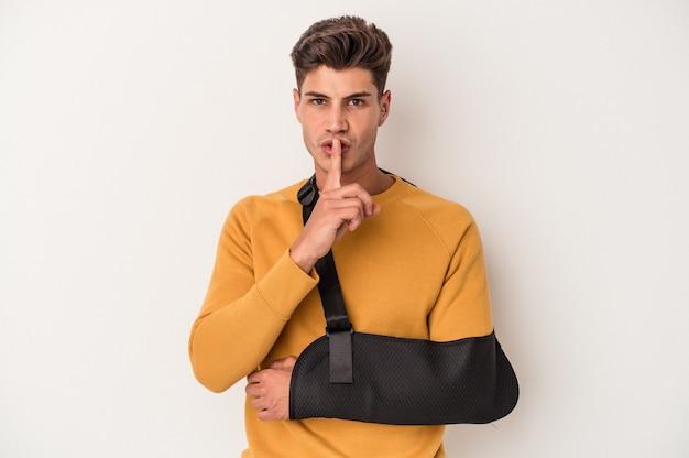 Молодой кавказский человек со сломанной рукой, изолированные на белом фоне, храня в секрете или прося молчания.