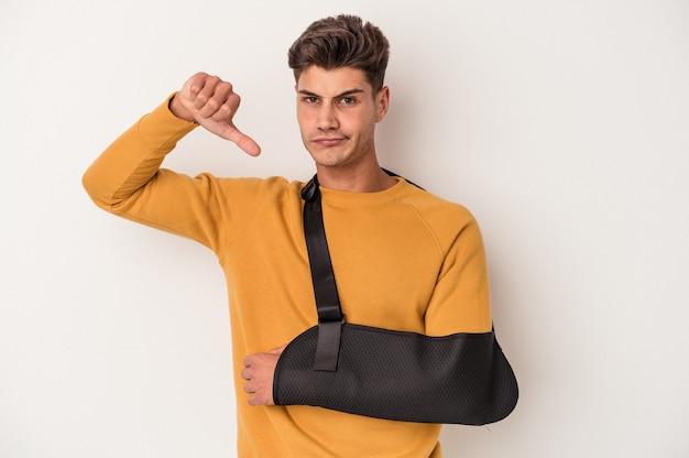 Молодой кавказский человек со сломанной рукой, изолированные на белом фоне, показывает жест неприязни, пальцы вниз. концепция несогласия.