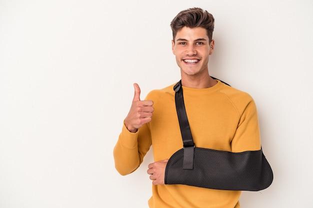 Молодой кавказский человек со сломанной рукой, изолированные на белом фоне, улыбается и поднимает большой палец вверх