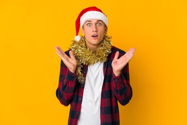クリスマスの帽子をかぶった若い白人男性は、黄色に分離されたプレゼントを持って驚いてショックを受けました。