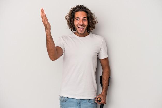 灰色の背景に松葉杖で隔離された若い白人男性は、嬉しい驚きを受け取り、興奮し、手を上げます。