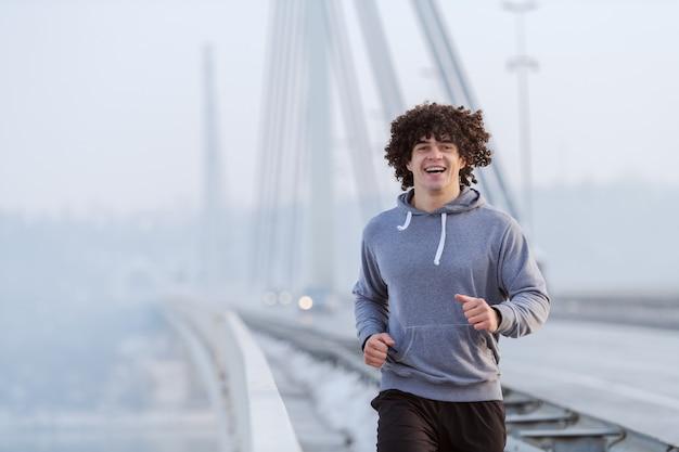 冬に橋の上を実行しているスポーツウェアに身を包んだ巻き毛を持つ若い白人男。健康的なライフスタイルのコンセプトです。