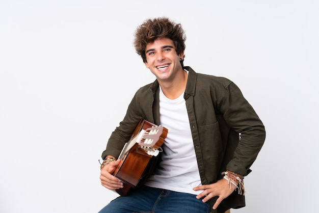 Young caucasian man with guitar over isolated white laughing
