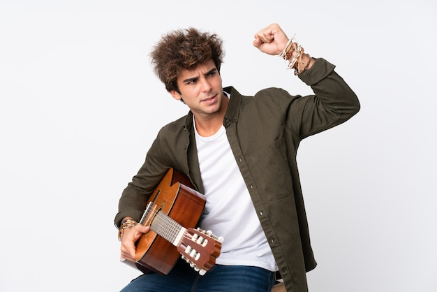 Young caucasian man with guitar over isolated white wall making strong gesture