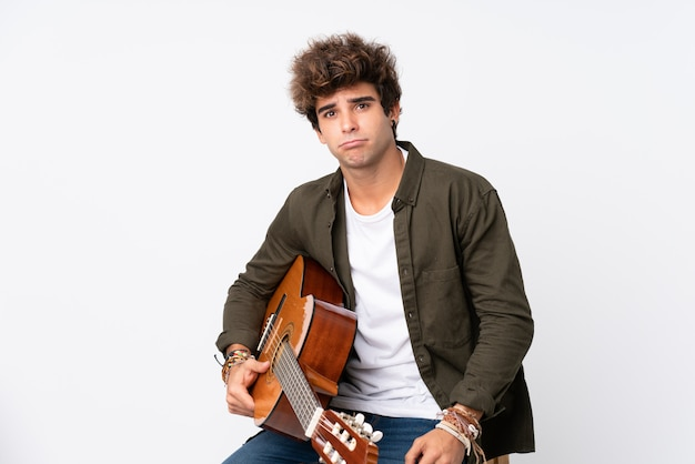 Young caucasian man with guitar over isolated white wall sad