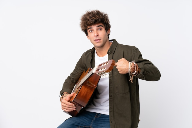 Молодой кавказский человек с гитарой над изолированной белой стеной с выражением лица сюрприза