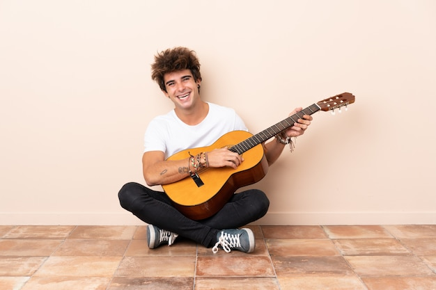 Young caucasian man with a guitar sitting on the floor smiling a lot