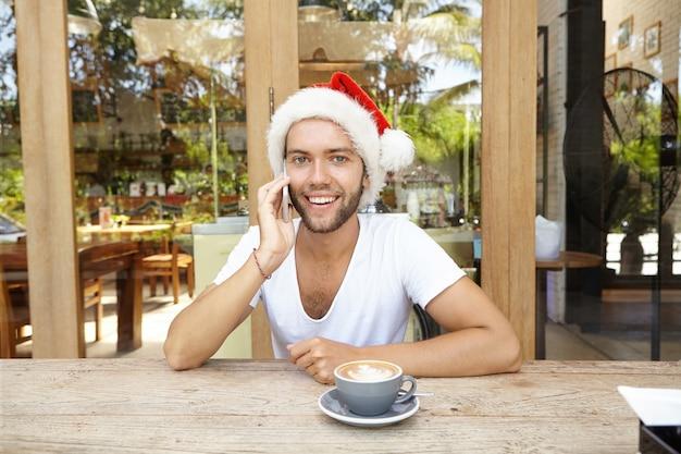 Giovane uomo caucasico con un sorriso attraente felice in cappello rosso con pelliccia bianca parlando al telefono cellulare con i suoi amici mentre beve il caffè al bar