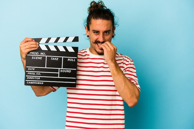 Young caucasian man with long hair holding clapperboard isolated on blue background biting fingernails, nervous and very anxious.