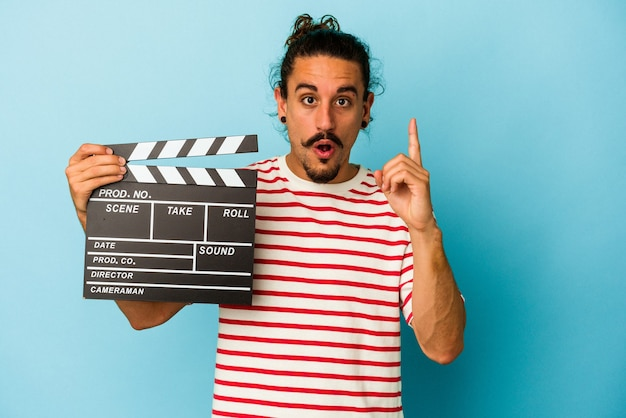 Young caucasian man with long hair holding clapperboard isolated on blue background having some great idea, concept of creativity.