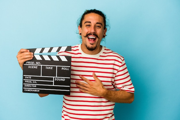 Young caucasian man with long hair holding clapperboard isolated on blue background laughs out loudly keeping hand on chest.