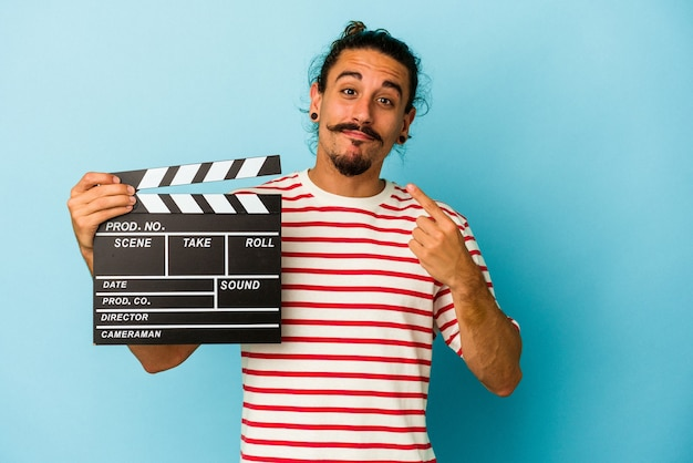 Young caucasian man with long hair holding clapperboard isolated on blue background pointing with finger at you as if inviting come closer.