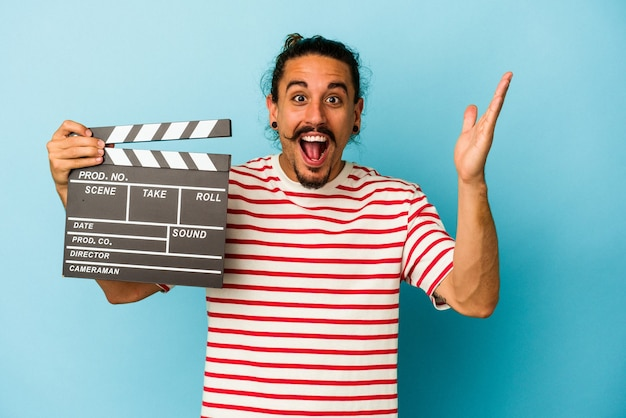 Young caucasian man with long hair holding clapperboard isolated on blue background receiving a pleasant surprise, excited and raising hands.