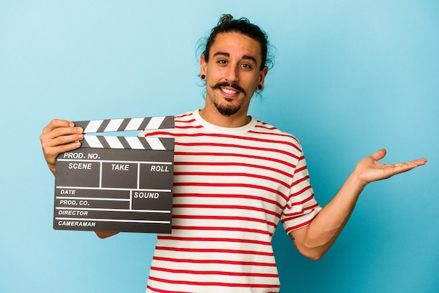 Young caucasian man with long hair holding clapperboard isolated on blue background showing a copy space on a palm and holding another hand on waist.