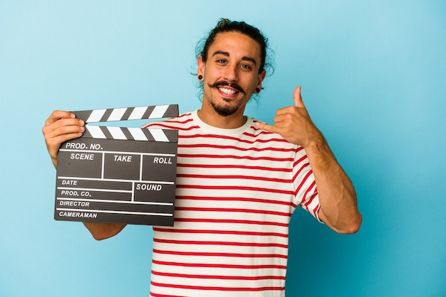 Young caucasian man with long hair holding clapperboard isolated on blue background showing a mobile phone call gesture with fingers.