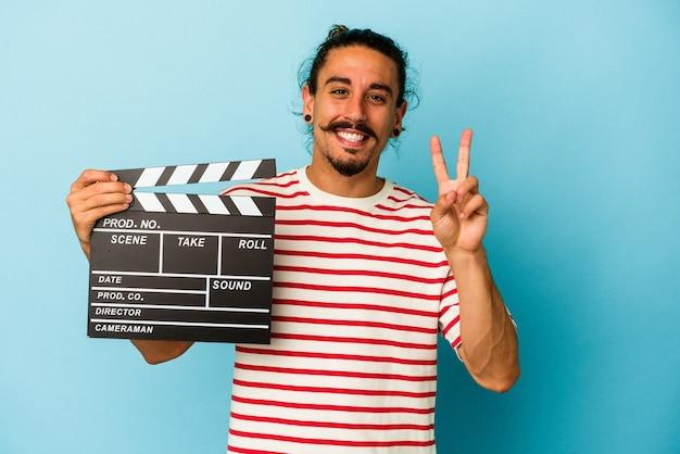 指で 2 番を示す青い背景に分離されたカチンコを保持している長い髪の若い白人男性。
