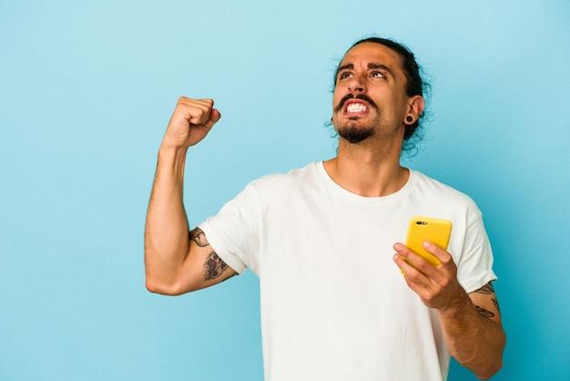 승리, 승자 개념 후 주먹을 높이 파란색 배경에 고립 된 휴대 전화를 들고 긴 머리를 가진 젊은 백인 남자.
