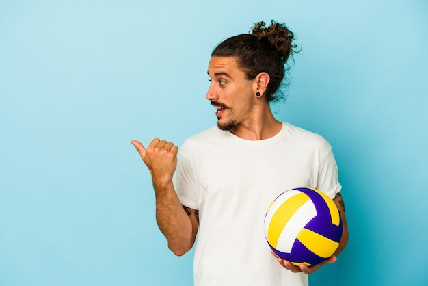 Young caucasian man with long hair isolated on blue background points with thumb finger away, laughing and carefree.