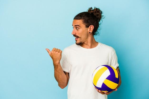 青い背景に長い髪の若い白人男性が、親指を離れて、笑い、屈託のないポイントをポイントします。