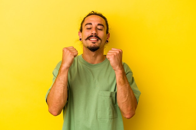 勝利、情熱、熱意、幸せな表情を祝う黄色い背景に長い髪の若い白人男性。