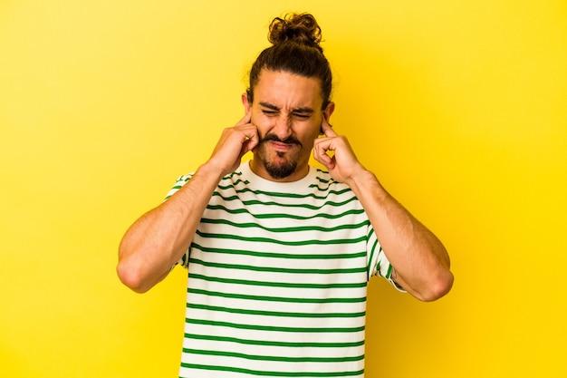손가락으로 귀를 덮고 노란색 배경에 고립 된 긴 머리를 가진 젊은 백인 남자 스트레스와 큰 주위에 의해 필사적.