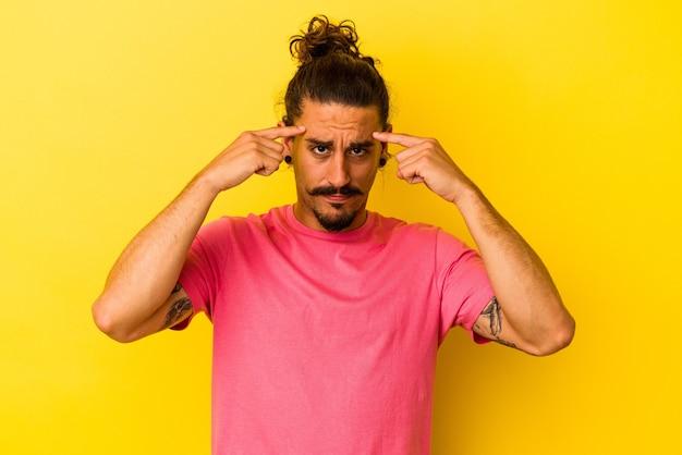 Молодой кавказский человек с длинными волосами, изолированными на желтом фоне, сосредоточился на задаче, держа указательные пальцы, указывая головой.