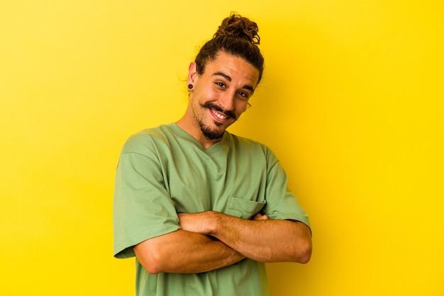 笑って、楽しんでいる黄色の背景に分離された長い髪の若い白人男性。