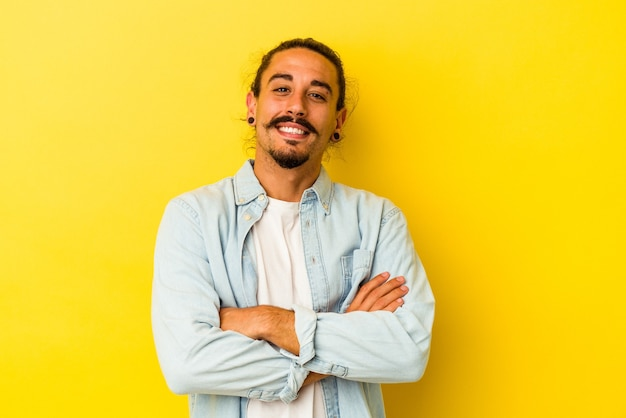 Молодой человек кавказской с длинными волосами, изолированными на желтом фоне, смеясь и весело.