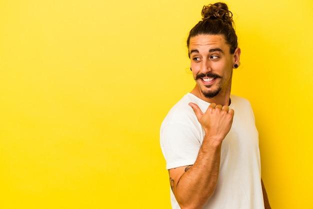 黄色い背景に長い髪の若い白人男性が、親指を離して、笑い、屈託のないポイントをポイントします。