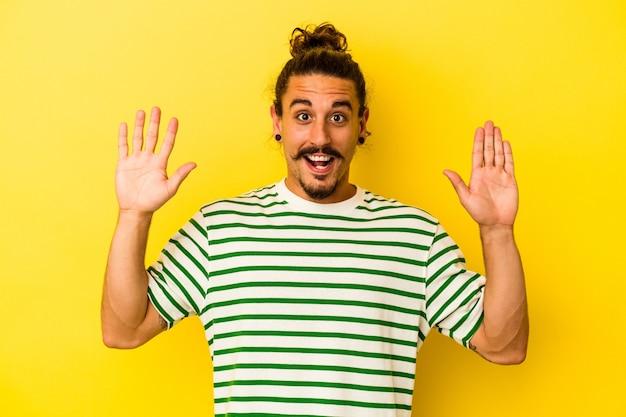 즐거운 놀라움을 받고, 흥분하고 손을 올리는 노란색 배경에 고립 된 긴 머리를 가진 젊은 백인 남자.