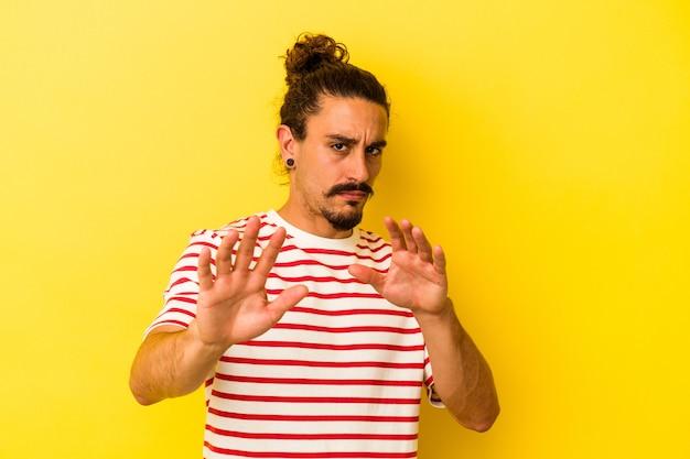 Молодой кавказский человек с длинными волосами, изолированными на желтом фоне, отвергая кого-то, показывая жест отвращения. Premium Фотографии
