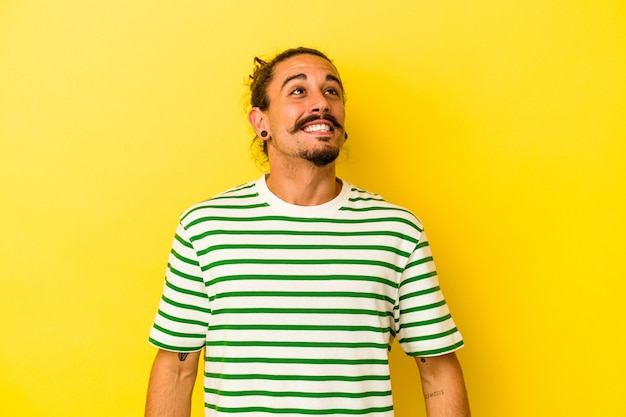 黄色の背景に長い髪の若い白人男性がリラックスして幸せに笑い、首を伸ばして歯を見せた。