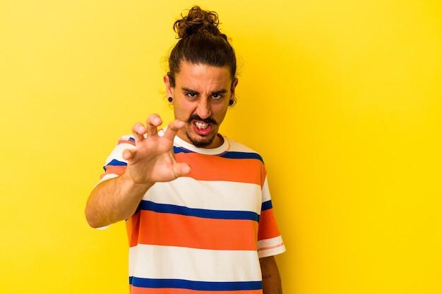 猫を模倣した爪、攻撃的なジェスチャーを示す黄色の背景に分離された長い髪の若い白人男性。