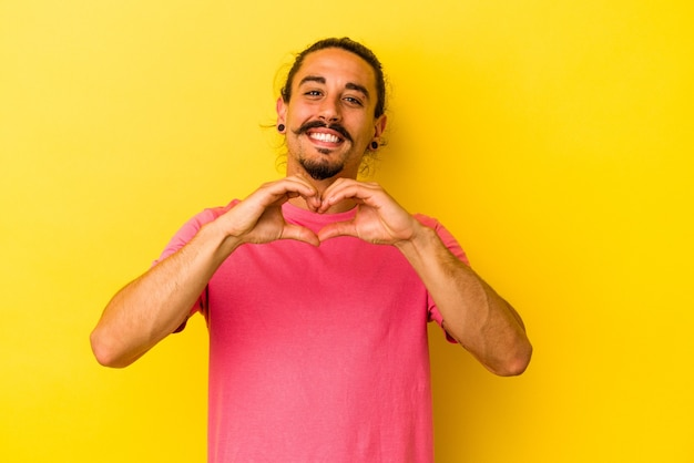 笑顔と手でハートの形を示す黄色の背景に分離された長い髪の若い白人男性。