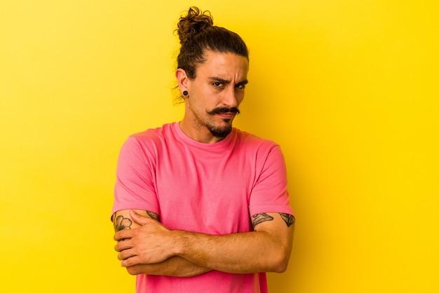 Молодой кавказский человек с длинными волосами, изолированными на желтом фоне, подозрительно, неуверенно осматривает вас.