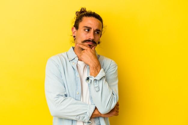 Молодой кавказский человек с длинными волосами, изолированными на желтом фоне, думает и смотрит вверх, будучи рефлексивным, созерцающим, имеющим фантазию.