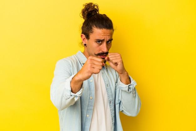 펀치, 분노, 인수, 권투로 인해 싸우는 던지는 노란색 배경에 고립 된 긴 머리를 가진 젊은 백인 남자.