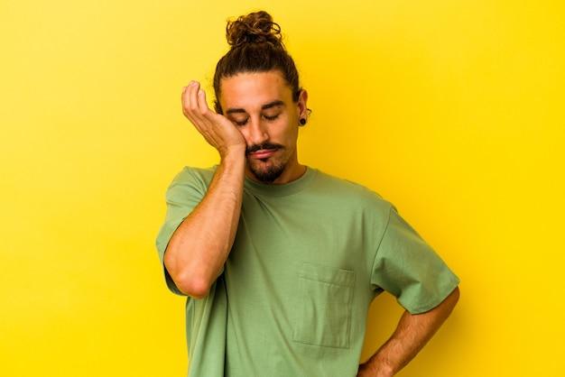 黄色の背景に分離された長い髪の若い白人男性は、頭に手をつないで疲れていて、とても眠いです。