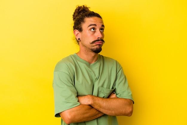 黄色の背景に分離された長い髪の若い白人男性は、繰り返しの作業にうんざりしています。