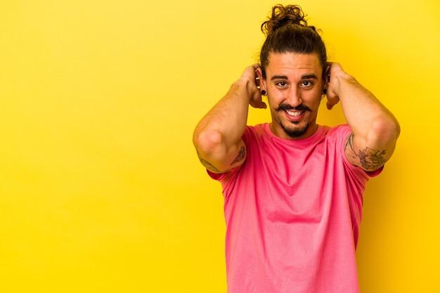 Молодой кавказский человек с длинными волосами, изолированными на желтом фоне, касаясь затылка, думая и делая выбор.