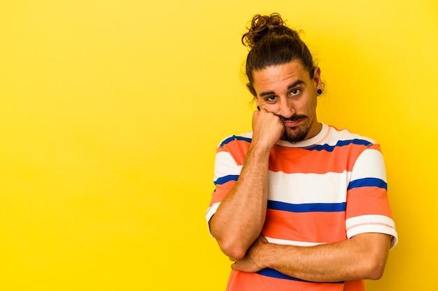 Молодой кавказский мужчина с длинными волосами, изолированными на желтом фоне, чувствует себя грустно и задумчиво, глядя на пространство для копирования.
