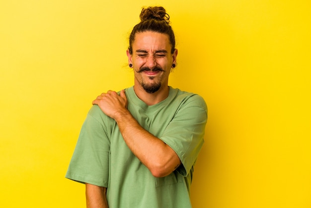 Young caucasian man with long hair isolated on yellow background having a shoulder pain.