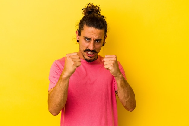 Young caucasian man with long hair isolated on yellow background showing fist to camera, aggressive facial expression.