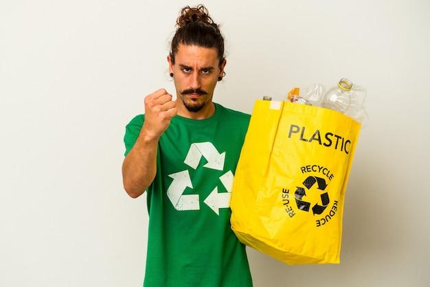 Молодой кавказский человек с длинными волосами, рециркулируя пластик, изолированные на белом фоне, показывает кулак на камеру, агрессивное выражение лица.