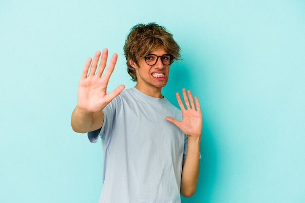 Young caucasian man with make up isolated on blue background  being shocked due to an imminent danger