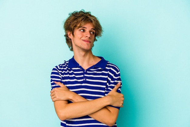 Young caucasian man with make up isolated on blue background  dreaming of achieving goals and purposes