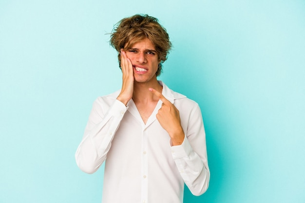 Young caucasian man with make up isolated on blue background  having a strong teeth pain, molar ache.