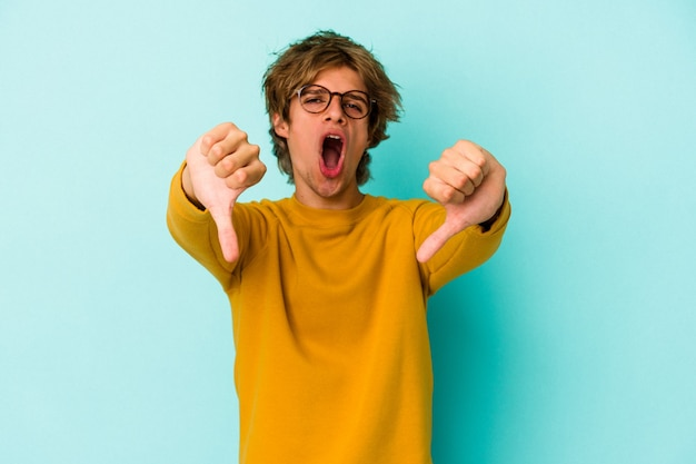 Young caucasian man with make up isolated on blue background  showing thumb down and expressing dislike.