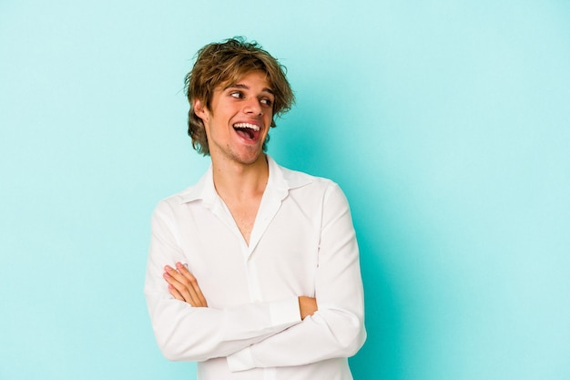 Young caucasian man with make up isolated on blue background  smiling confident with crossed arms.
